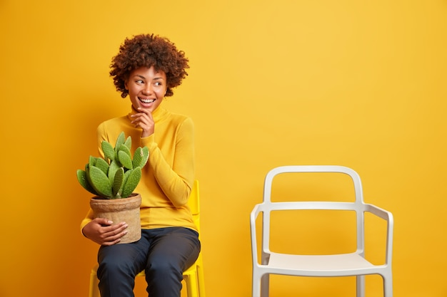 Cheerful curly haired woman smiles broadly keeps hand on chin holds pot of green cactus has happy mood hears something very positive dressed casually poses near empty chair