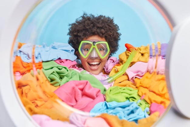 Cheerful curly haired young busy woman wears snorkeling mask for diving has lot of laundry to make does housework drowned in multicolored clothes against blue wall