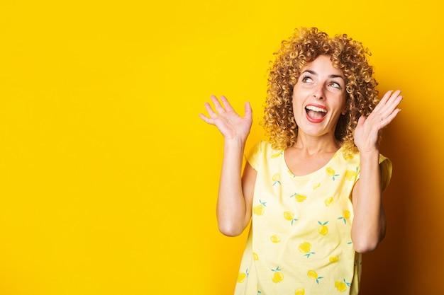 黄色の背景に手のジェスチャーを作って笑っている陽気な縮れ毛の若い女性