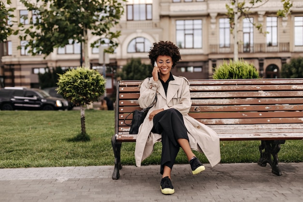 Cheerful curly lady in black pants and beige trench coat sits on wooden bench outdoors