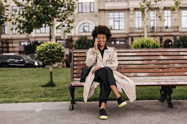 검은색 바지와 베이지색 트렌치 코트를 입은 쾌활한 곱슬머리 여성이 야외 나무 벤치에 앉아 있다