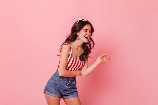 Веселая кудрявая дама в летнем наряде искренне смеется на розовой стене