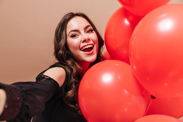 Allegra signora riccia sorride, guarda nella fotocamera e prende selfie con palloncini.