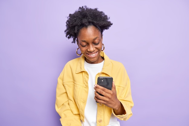 Cheerful curly teenage girl uses mobile phone for making shopping online or texting messages smiles happily has glad expression