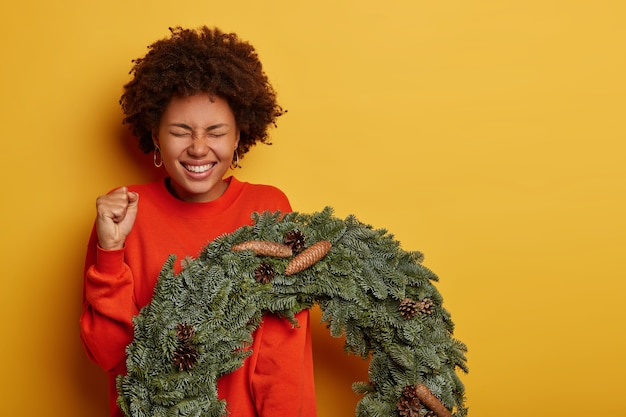 Cheerful curly woman clenches fist, anticipates miracle happen, holds beautiful christmas wreath