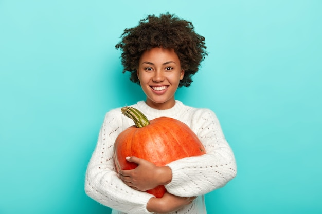 Cheerful curly woman embraces ripe pumpkin, smiles pleasantly, dressed in white sweater