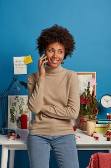 쾌활한 곱슬 여자는 캐주얼 한 옷을 입고 전화 대화를하고, 이빨 미소로 옆으로 보입니다.