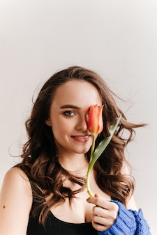 Cheerful curly woman sincerely smiles and holds red tulip. blue-eyed girl in black tee poses on isolated background.