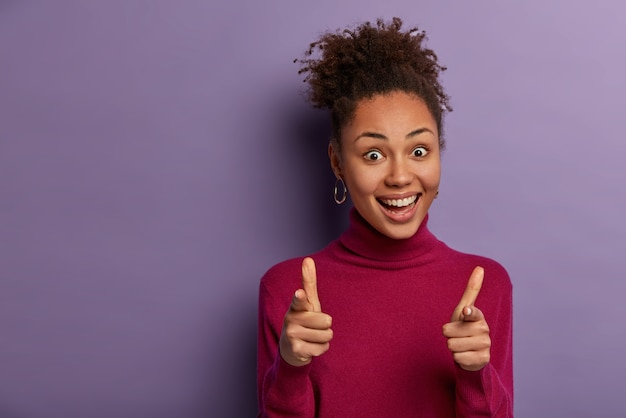Cheerful curly woman with friendly positive expression points index fingers