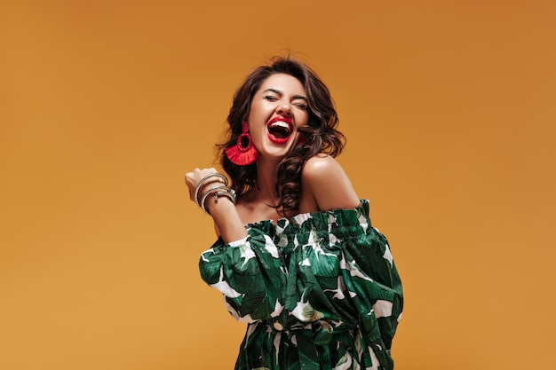 Cheerful curly woman with red lipstick and modern earrings in green cool sundress laughing and posing with closed eyes on isolated wall