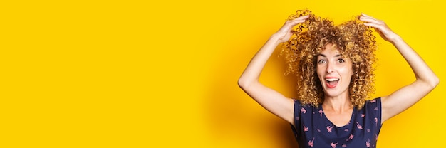 Cheerful curly young woman lifts her hair up on a yellow background. banner.