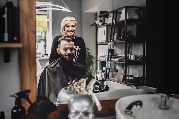 Cheerful customer and barber in shop