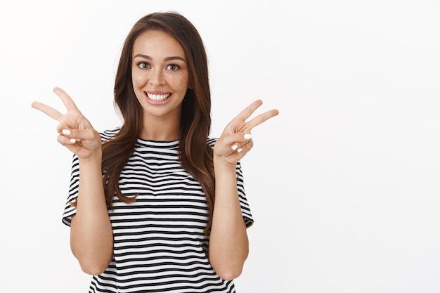 Веселая милая и веселая жизнерадостная молодая девушка с веснушками в полосатой футболке делится позитивом, дружелюбно улыбается и демонстрирует добрую волю, мир или знак победы, беззаботно стоящая у белой стены