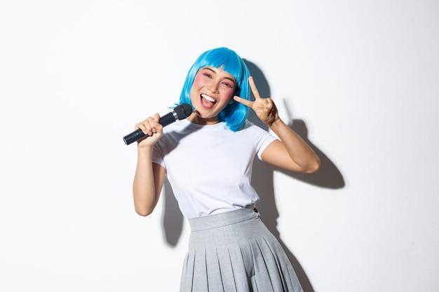 파란색 가발을 쓰고 할로윈 파티를위한 애니메이션 캐릭터로 차려 입은 쾌활한 귀여운 아시아 소녀