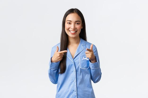 幸せに笑って、幸せに笑って、ガールフレンドをジャマで寝坊パーティーに招待する青いパジャマに立って、自信を持って楽しい表情でカメラに指を向ける、白い背景の陽気なかわいいアジアの女の子