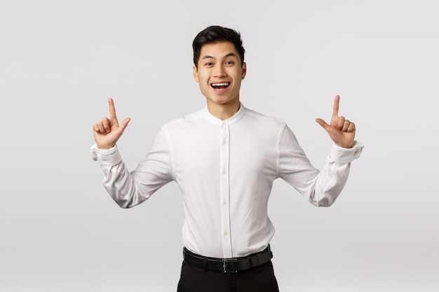 Cheerful cute asian guy celebrating birthday inviting guests see fireworks. man rejoicing as standing in suit, pointing up, smiling happy and entertained, found product he liked,