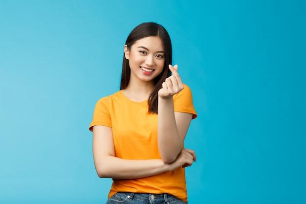 陽気なかわいいアジアの女性の暗い短いヘアカット、指で韓国のハートのサインを表示し、嬉しそうに笑って、同情と思いやりのある気持ちを表現し、愛のスタンド青い背景を告白し、明るい笑顔