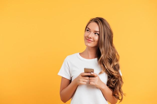 Веселая милая красивая молодая женщина в чате по мобильному телефону