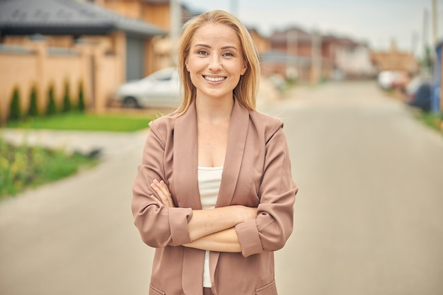 Cheerful cute blonde woman with folded arms looking at the camera