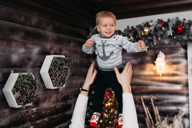 Веселый милый мальчик в сером свитере смеется и играет с родителями в рождественской студии зимой
