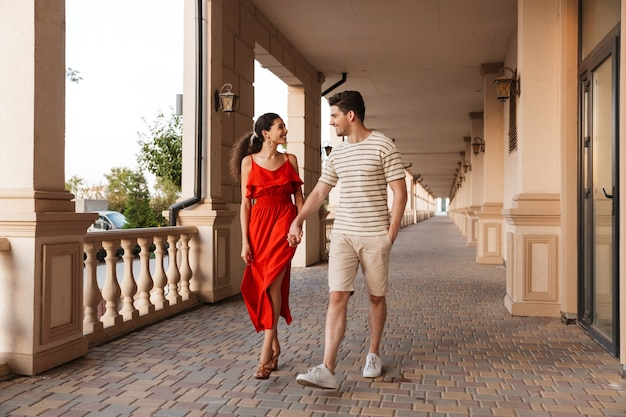 Cheerful cute couple holding hands together and smiling while walking near beautiful building