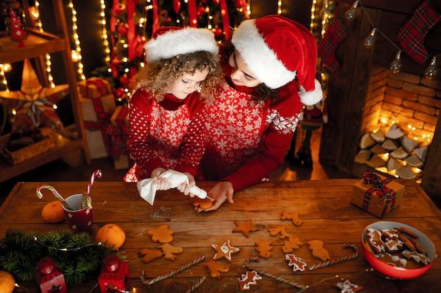 Веселая милая кудрявая маленькая девочка и ее старшая сестра в шляпах санта готовят рождественские печенья