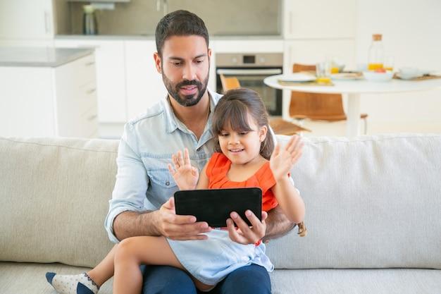 陽気なかわいい女の子と彼女のお父さんがオンラインアプリを使用するか、タブレットで映像を一緒に見ています。