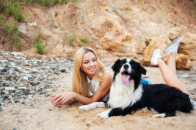 Cheerful cute girl lying and relaxing with her dog on the beach