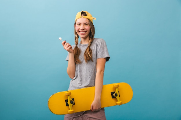 Cheerful cute girl standing isolated, holding skateboard