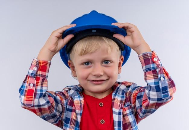 Un ragazzino sveglio allegro con capelli biondi che indossa la camicia a quadri che tiene il suo casco blu mentre guarda su un muro bianco