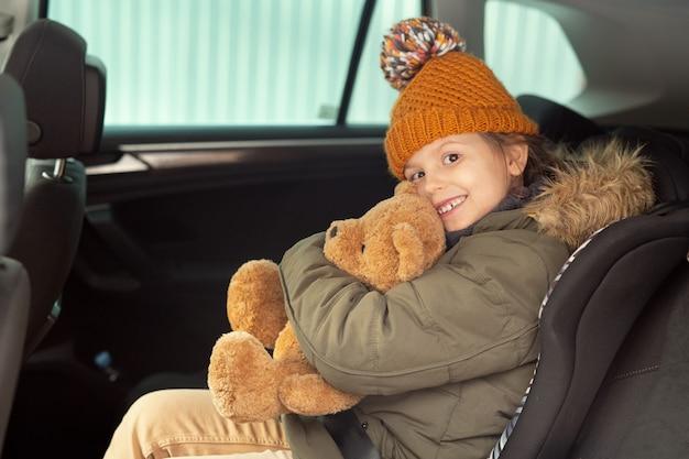 따뜻한 겨울옷을 입은 쾌활한 귀여운 소녀가 부드러운 갈색 테디베어를 안고 차 뒷좌석에 앉아 당신을 바라보고 있습니다