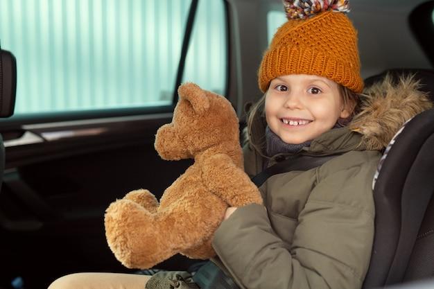따뜻한 겨울옷을 입은 쾌활한 귀여운 소녀가 부드러운 갈색 테디베어를 들고 카메라 앞 차 뒷좌석에 앉아 당신을 바라보고 있습니다