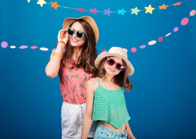 Веселые милые маленькие девочки в солнцезащитных очках стоят и позируют на синем фоне