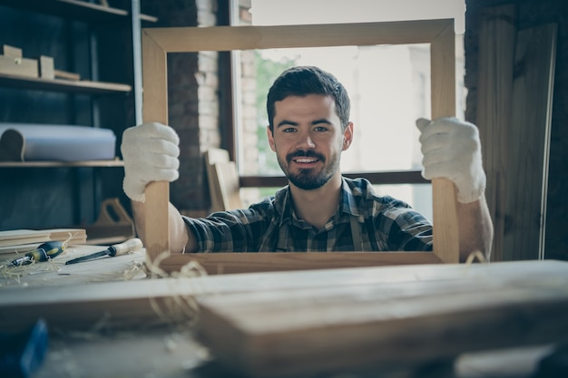 Cheerful cute man having finished making frame holding it looking through wooden handmade smiling toothily