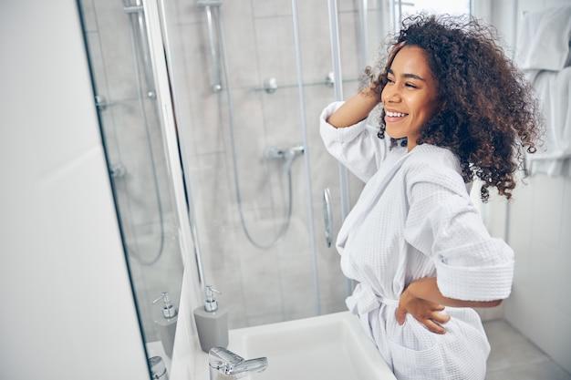 거울 앞에 그녀의 두꺼운 곱슬 머리를 감탄하는 쾌활한 귀여운 현대 여성