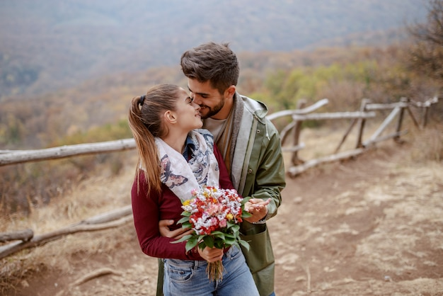 Cheerful cute multicultural couple dressed casual standing in nature and hugging.