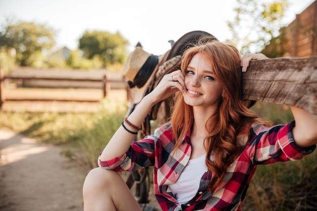 쾌활한 귀여운 빨간 머리 카우걸 앉아서 목장 울타리에 쉬고