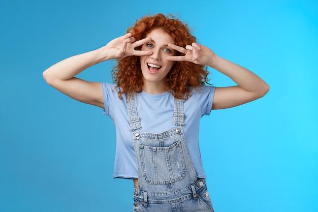 陽気なかわいい赤毛生姜の女の子巻き毛のヘアカットショー積極性平和勝利の兆候広く笑っている目は楽しい遊び心のある愚かな子供っぽいムードウェアデニム夏のオーバーオール青い背景を持っています。