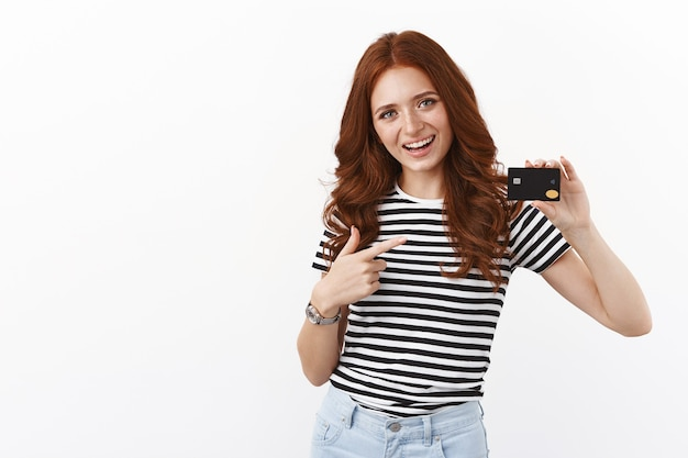 Una ragazza rossa allegra e carina ha aperto un deposito per raccogliere soldi per le vacanze estive, indicando la carta di credito nera e sorridendo con gioia, pagando online, usando il cashback per pagare il caffè