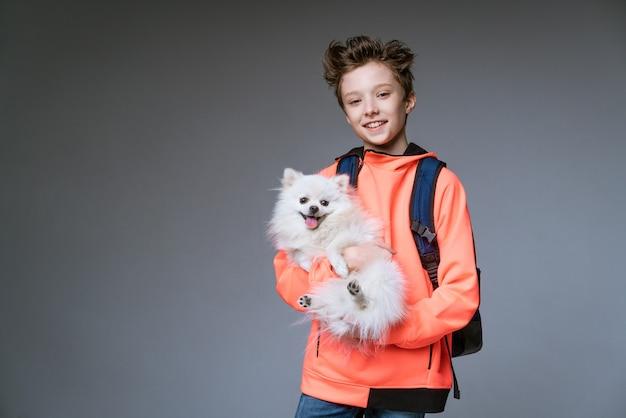 배낭과 회색 벽 포즈에 그의 손에 개 밝은 옷을 입고 백인 민족의 쾌활한 귀여운 남학생
