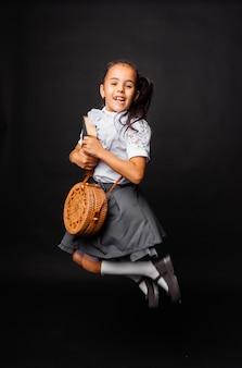 Веселая милая школьница держит книгу и круглую сумку и прыгает на темном фоне.