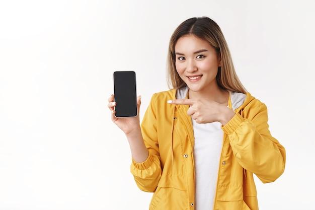Веселая милая нежная азиатская блондинка в желтой стильной куртке держит показ смартфона, указывая указательным пальцем на экране телефона, широко улыбаясь, рекомендую крутое приложение, стоящее на белой стене