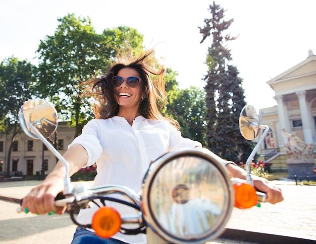 スクーターを運転する陽気なかわいい女性