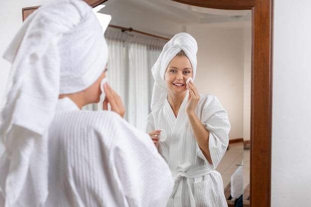 Веселая милая женщина в белом вафельном халате с полотенцем на голове