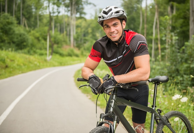 Cheerful cyclist male leaning on his bike on the forest road