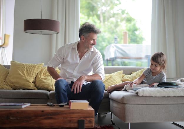 ソファの上のフォトアルバムの写真を見ている陽気なお父さんと彼の子供