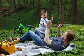 Cheerful dad and son have fun playing on the plaid in a green park