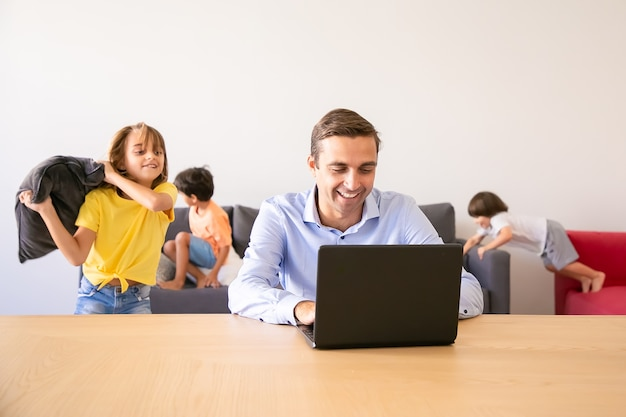 Papà allegro che chiacchiera tramite laptop e bambini che giocano con i cuscini vicino a lui. padre caucasico che lavora a casa durante le vacanze scolastiche. famiglia e concetto di tecnologia digitale