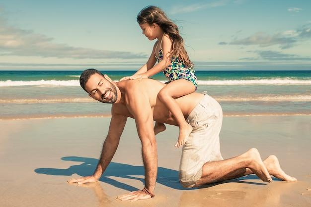 Papà allegro che va sulle mani e sulle ginocchia sulla spiaggia, portando la bambina sulla schiena