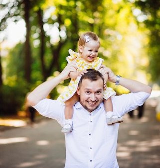 Cheerful dad holds his daughter on the neck